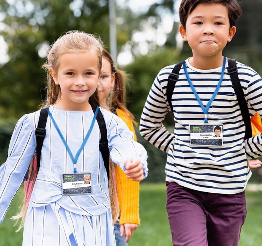deux enfants marchant vers leur école et portant leur badge scolaire