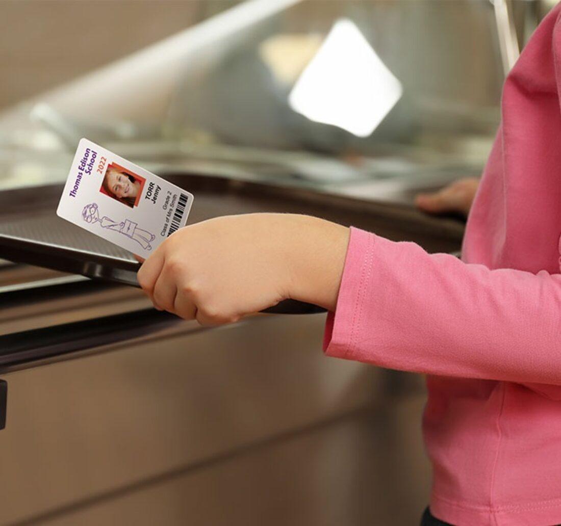 enfant tenant son plateau et sa carte de cantine personnalisé grâce à l'imprimante Badgy