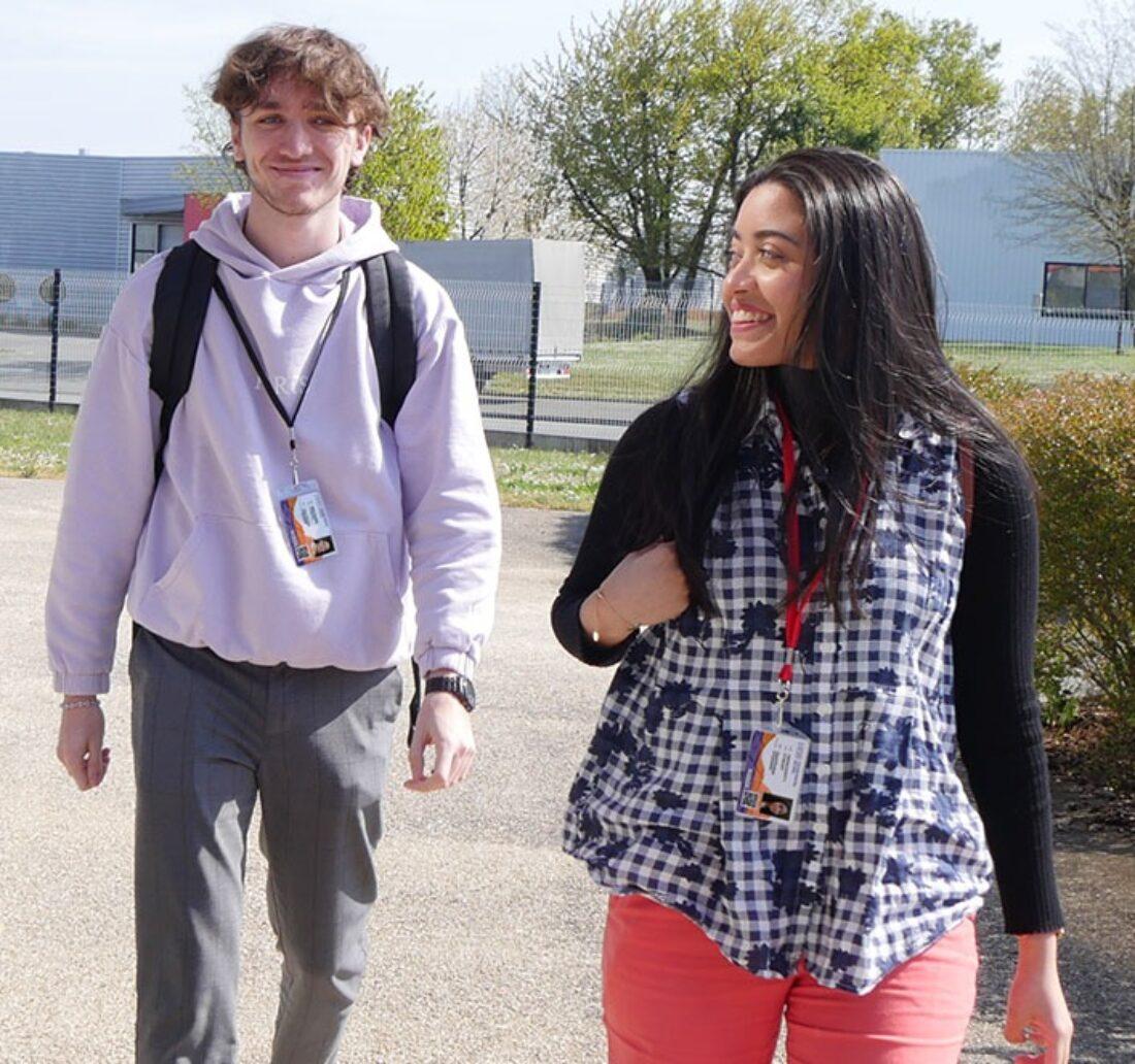 Deux étudiants marchant vers leur école avec leur carte d'identification autour du cou