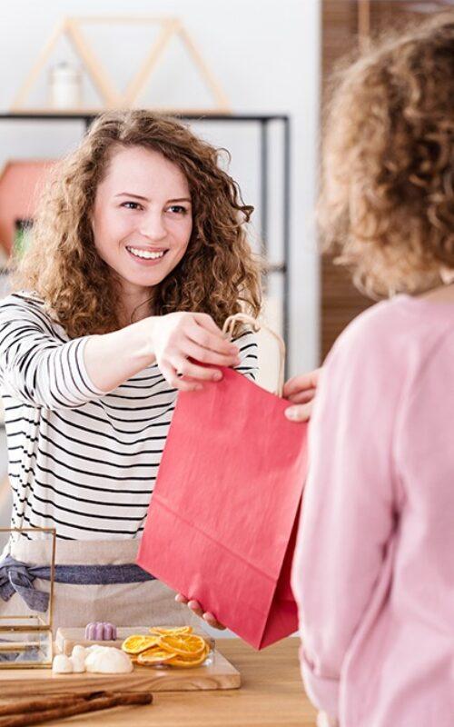 Vendeuse remettant un sac dans son commerce utilisant badgy pour créer ses cartes de fidélité
