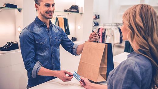 Acheteuse tendant au commerçant sa carte privilèges créée avec l'imprimante Badgy