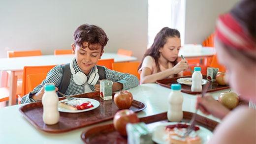 Enfants déjeunant à la cantine et identifié grâce à une carte personnalisée Badgy